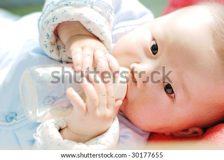 baby feeding himself with fruit juice - stock photo