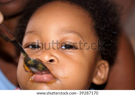 baby feeding with food filled face - stock photo