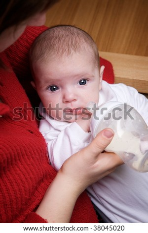 Baby feeding, with milk on her chin - stock photo