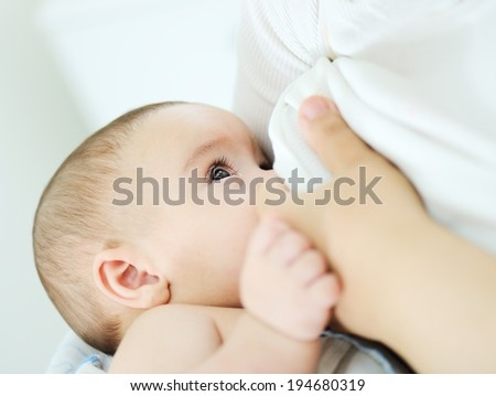 Baby feeds on mother's breasts milk - stock photo