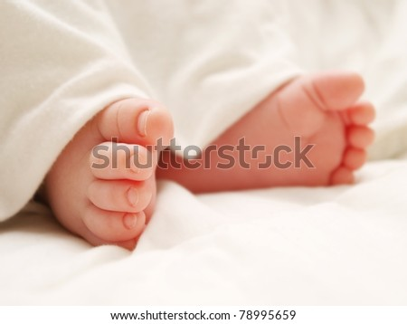 Baby feet covered in white sheet, isolated in white - stock photo