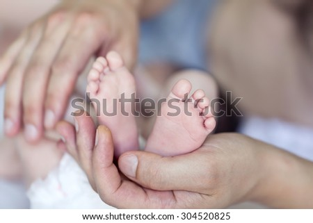 Baby feet cupped into father hands