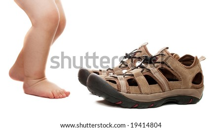 Baby feet eager to try on huge adult shoes, isolated - stock photo