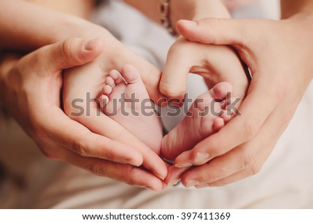 Baby feet heart: little feet in mom's and dad's hands - stock photo