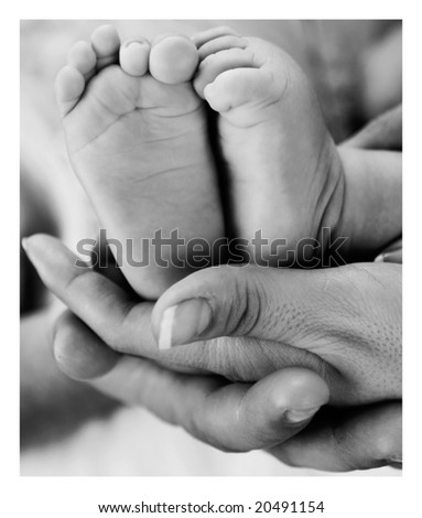 Baby feet held by mother's and father's hand - stock photo