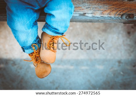 baby feet in fashionable jeans and shoes on the bench - stock photo