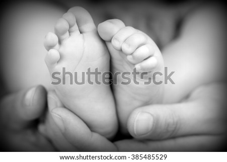 Baby feet in father hands - stock photo