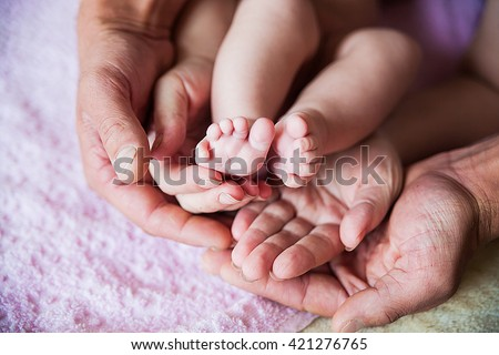 Baby feet in father hands on purple