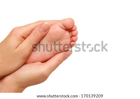 Baby feet in female hands - stock photo