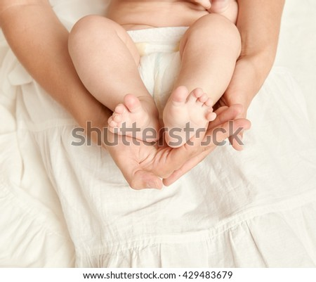 baby feet in mother hand, health care concept, body and skin, yellow toned - stock photo
