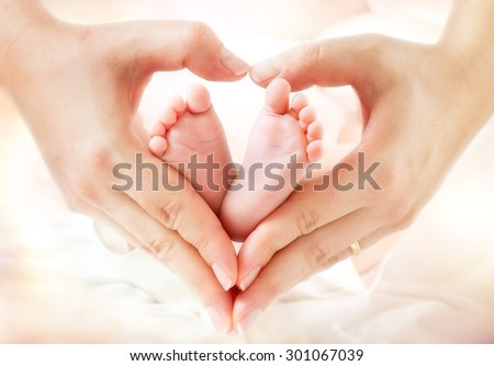 baby feet in mother hands - hearth shape  - stock photo