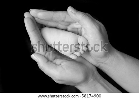 Baby feet in mother's hand forming heart shape black and white - stock photo