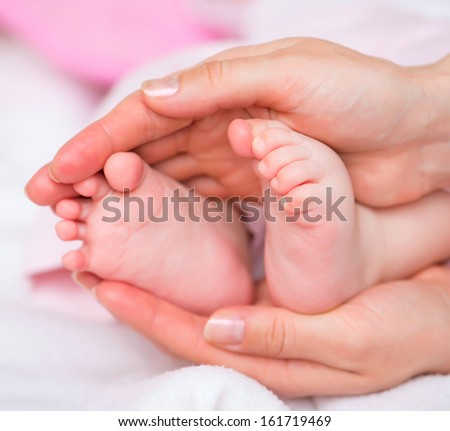 baby feet in mothers hands - stock photo