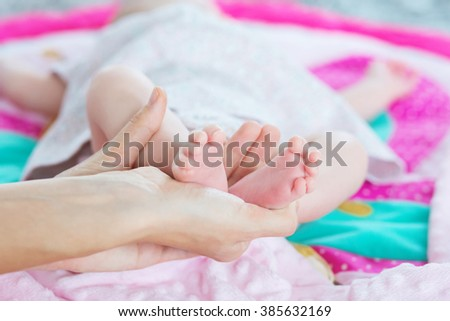 baby feet in reliable hands of the massage therapist, selective focus, natural light - stock photo