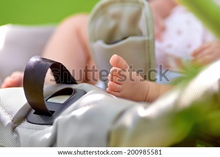 Baby feet in the child stroller - stock photo
