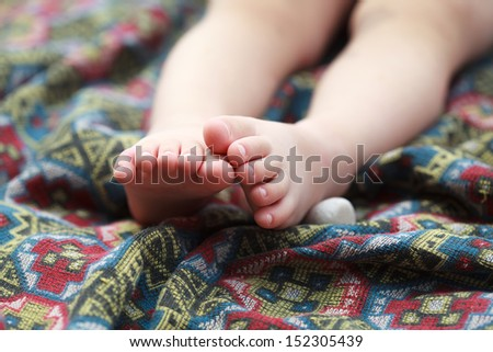 baby feet on a colorful bedspread with a geometric pattern, selective focus - stock photo