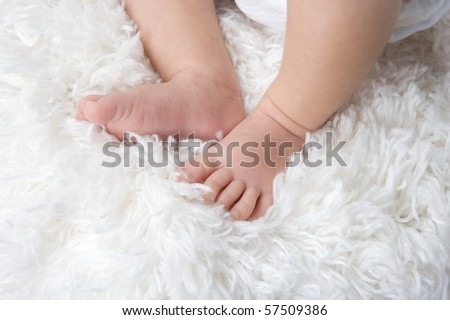 Baby feet on a white carpeted rug - stock photo