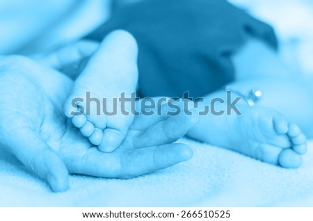 Baby feet on the mothers hand - stock photo