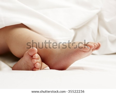 baby feet on white sheet