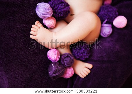 baby feet with balls of yarn
