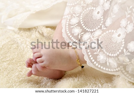 Baby feet with ceremonial clothes. Baptism clothes.