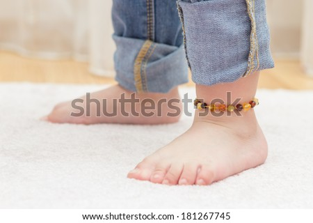 Baby feet with colorful amber anklet - stock photo