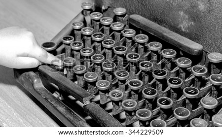 baby finger put the close up old typewriter - stock photo