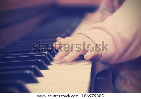 baby fingers playing the piano. Photo in retro style - stock photo