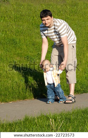 baby first steps with father - stock photo