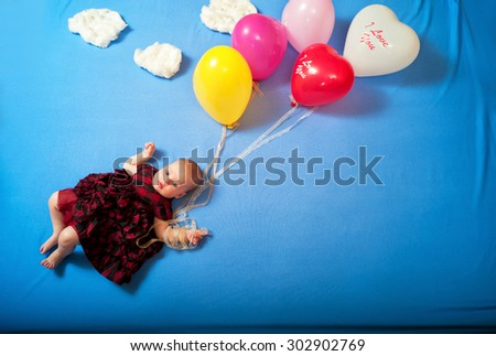 Baby flies on balloons in the clouds lying on the bed - stock photo