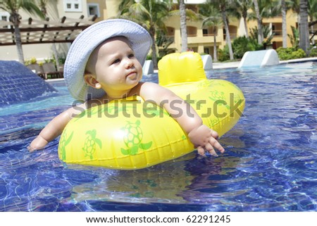 Baby floating and swimming in a tropical resort pool - stock photo