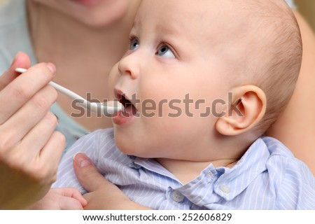 Baby food, baby eating. Mother feeding her baby boy by spoon. - stock photo