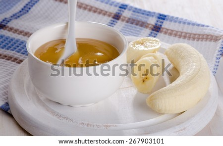 Baby food - bananas puree in  white bowl. Selective focus - stock photo