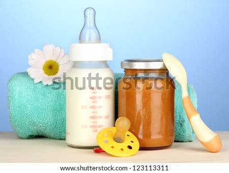 Baby food, bottle of milk and puree  on blue background - stock photo