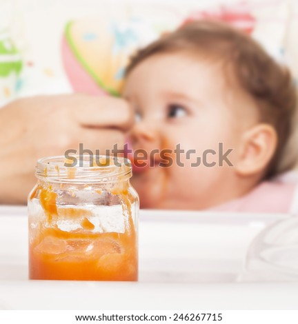 Baby food in the jar with baby in the background - stock photo