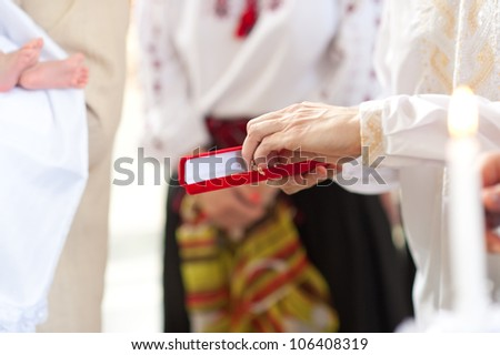 baby foot and crucifix in red box in hand - stock photo