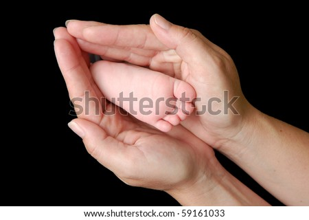 Baby foot in mother's hand forming heart shape - stock photo