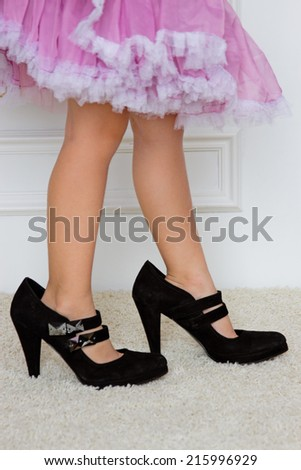 Baby foot in women's high-heeled shoes. close-up - stock photo