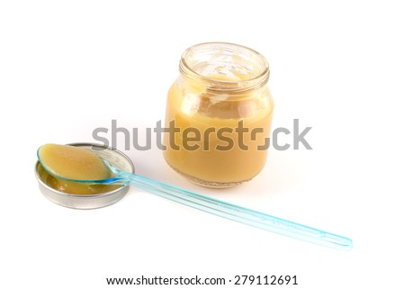 Baby fruit puree in the pot with a plastic spoon on a white background - stock photo