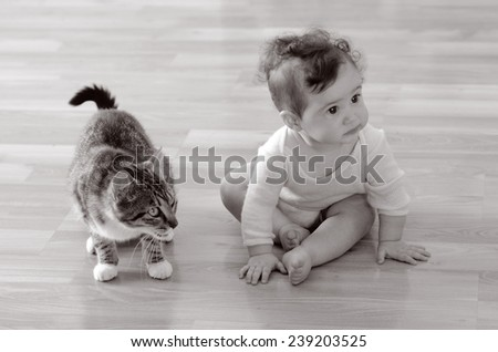 Baby (girl age 06 months) sits with animal (domestic cat) at home. Concept photo animals and children. (BW) - stock photo