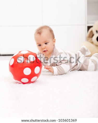 Baby girl amazed by red ball - stock photo
