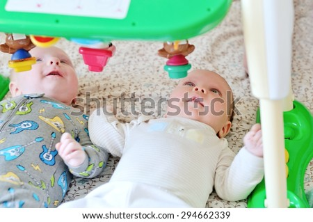 baby girl and baby boy are looking on the toy - stock photo