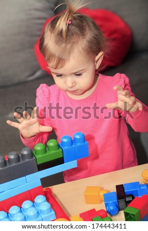 Baby girl and blocks - stock photo