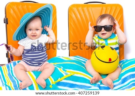 Baby girl and boy twins packed for travel with orange luggage bags - stock photo