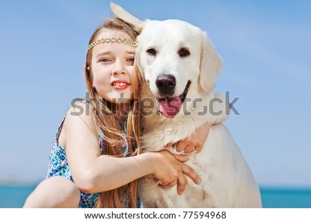 Baby girl and dog playing in the sea - stock photo
