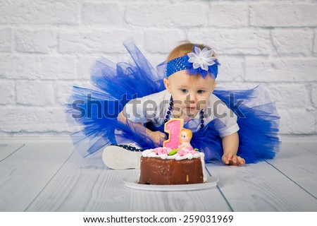 Baby girl and her birthday cake on the floor