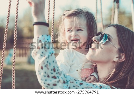 baby girl and her mom swinging from a swing in the park - stock photo