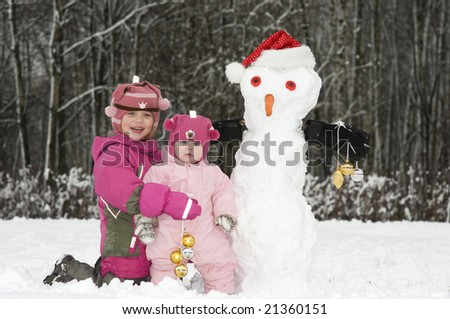Baby Girl and her smiling sister with Funny Snowmen in Santa Hat. Copy space for your text. - stock photo
