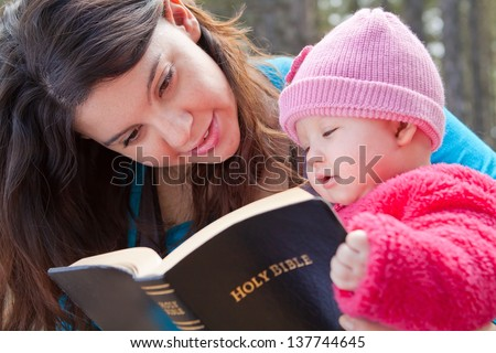 Baby girl and mom reading KJV Bible (King James Version) - stock photo