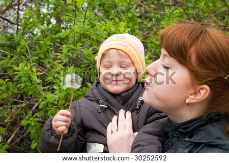 baby girl and mother blow to the dandelion
